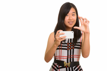 Young happy Asian businesswoman focusing while taking picture wi