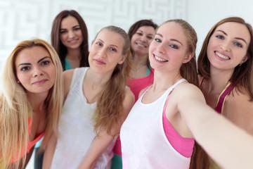 Young happy women dressed in sportswear taking selfie
