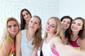 Group of young attractive women dressed in sportswear taking selfie