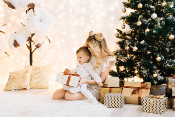 Happy family at home in front of the tree. Beautiful mother with a child open gifts. A woman and a little boy are preparing for the new year holidays