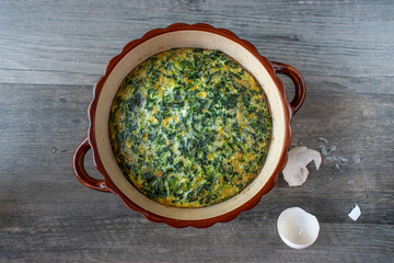 spinach souffle in rustic round dish with egg shells flat lay