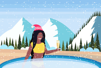 woman hold champagne relax in outdoor swimming pool luxury resort snowy mountains fir tree forest landscape background winter vacation concept flat horizontal