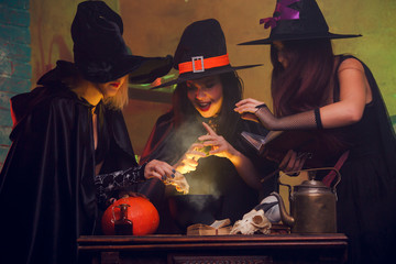 Image of three witches in hats with book of potions making potions in cauldron