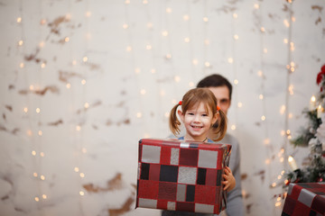 Photo of girl with dad and box with gift on background of New Year's decorations