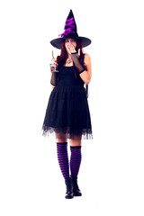 Full-length image of surprised witch with wine glass with wine in black dress, striped socks