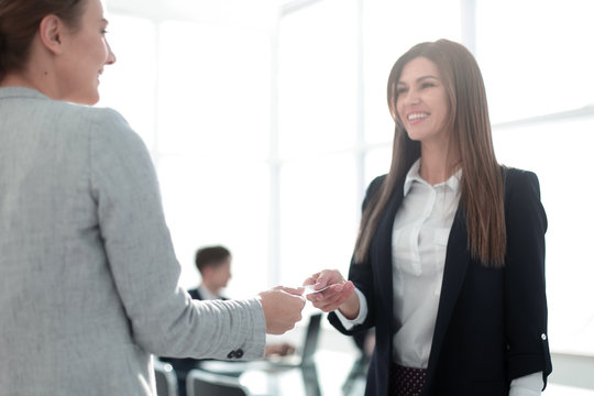 two successful businesswomen exchange their business cards