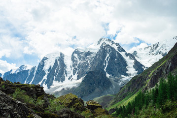 Snowy mountain top behind rocky mountains under cloudy sky. Rocky slope above forest. Clouds above glacier. Atmospheric landscape of majestic nature of highlands.
