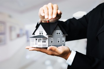 Male hands holding house model on background