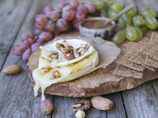Baked Camembert on wooden board, branch of green and red grapes, rosemary, rye bread, nuts and honey. Close up, copy space, selective focus