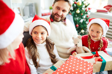 Pretty siblings, their mom and dad in Santa caps having discussion of plans for xmas vacation