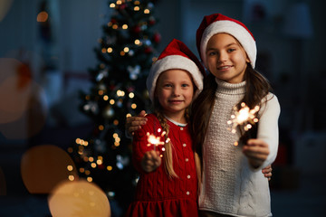 Two little Santa girls with burning bengal lights looking at you on background of decorated firtree