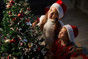 Two little sisters in Santa caps looking at decorated xmas tree on holy night