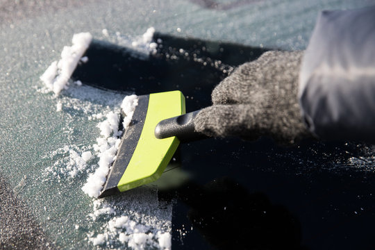 Hand in glove cleans window of the car from ice