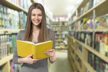 Young female student on blurred library background
