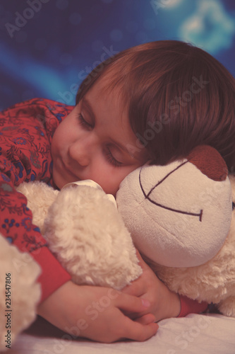 34c47669987e Little cute child girl hugs the teddy bear and sleeps on bed in her bedroom,  happy little girl, family home concept.happy carefree childhood. Retro  styled.
