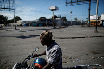 A man riding a motorbike passes by a blocked crossroad during the second day of a general strike in Port-au-Prince