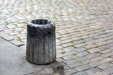 Trash bag in a concrete bin mounted on a pedestrian pavement of paving stones with copy space for text.
