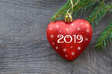 2019 New Year greeting card with red Christmas heart and fir tree branch on old wooden background.Winter holidays festive decoration with copy space.Selective focus.