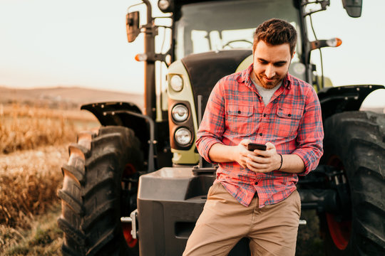 Portrait of smiling farmer using smartphone and tractor at harvesting. Modern agriculture with technology and machinery concept