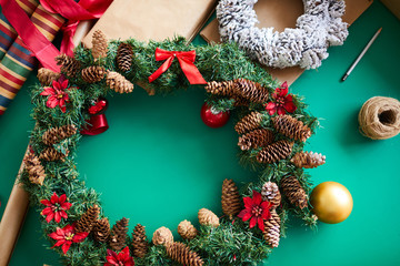 Christmas background with handmade coniferous wreath decorated with red flowers, bows and cones