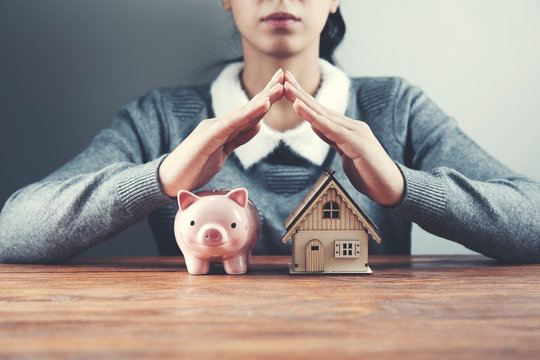 woman hand house model and piggy bank