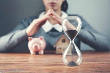 woman hand house model and piggy bank with clock