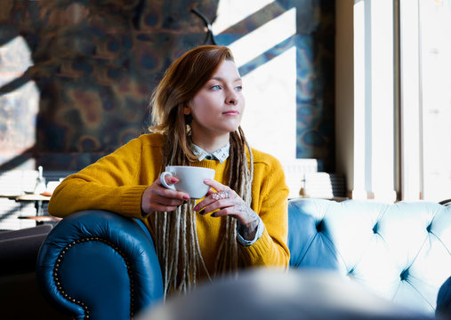 young hipster girl in knitted sweater enjoying drinking coffee