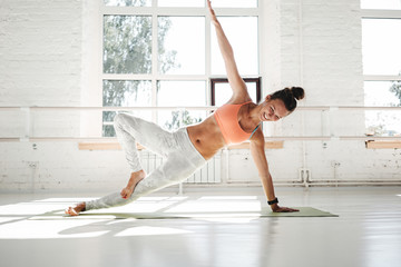 Fit strong woman doing stretching sitting on yoga mat in white gym. Athletic woman workout early morning