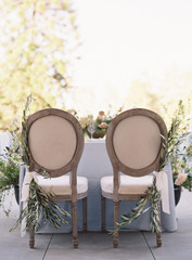 The backs of two chairs at a wedding reception