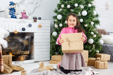 Festive little girl opening a gift at home in the living room