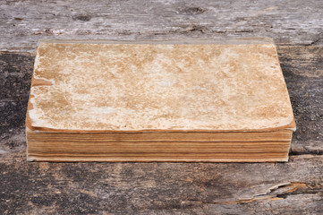 The old shabby book lies on a wooden background. Front view.
