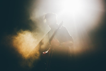 Guitarist silhouette on a stage in a backlights in the smoke playing rock music