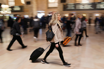 A woman pulls her luggage though Grand Central Terminal in New York