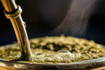 Steaming yerba mate in a traditional calabash gourd