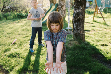 Girl with her palms up while her brother stands behind her