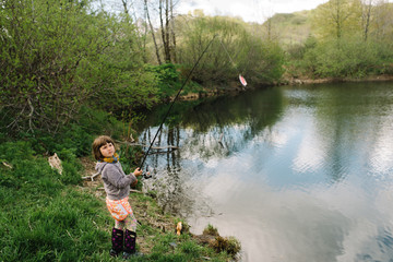 Young girl holding a fishing pole with bait hooked onto it