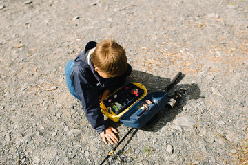 Young boy looking through a tackle box