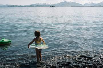 Young girl wearing an inflatable swim ring in the water