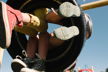 Three children on a tire swing