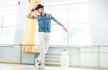 Young Street dancer dressed in jeans waistcoat and hat training the new dance in the gym hall with wide sunny windows