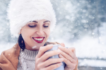 Happy smiling Woman with cup of hot tea in snow forest