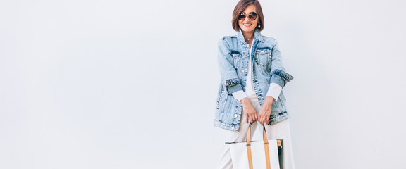 Wall Mural - Elegant woman dressed in oversize denim jacket and wide white trousers