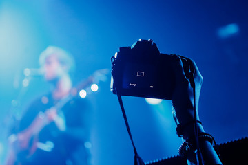 Professional dslr camera at music concert in raised up hand recording singer on a stage
