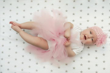 cute little ballerina with round cheeks, a fluffy pink skirt and a flower on her head. Baby Health