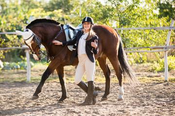 Girl equestrian rider stands near the horse. Horse farm. Horse raises his leg. Horse theme     Papier Peint