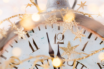 vintage alarm clock is showing midnight. It is twelve o'clock, christmas and bokeh, holiday happy new year festive concept on light bokeh background