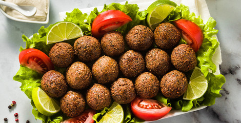 banner of vegan falafel with cashew cheese sauce on a table with chopped tomatoes and lime slices. healthy food for the whole family or party
