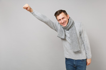 Cheerful young man in gray sweater, scarf with outstretched hand like Superman isolated on grey background. Healthy fashion lifestyle, people sincere emotions, cold season concept. Mock up copy space.