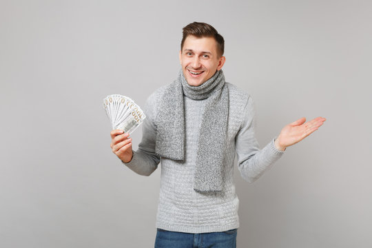 Excited young man in gray sweater, scarf hold lots bunch of dollars banknotes cash money pointing hand aside isolated on grey background. Healthy lifestyle people sincere emotions cold season concept.