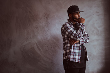 Pensive African-American bearded man standing next to a gray textured wall.